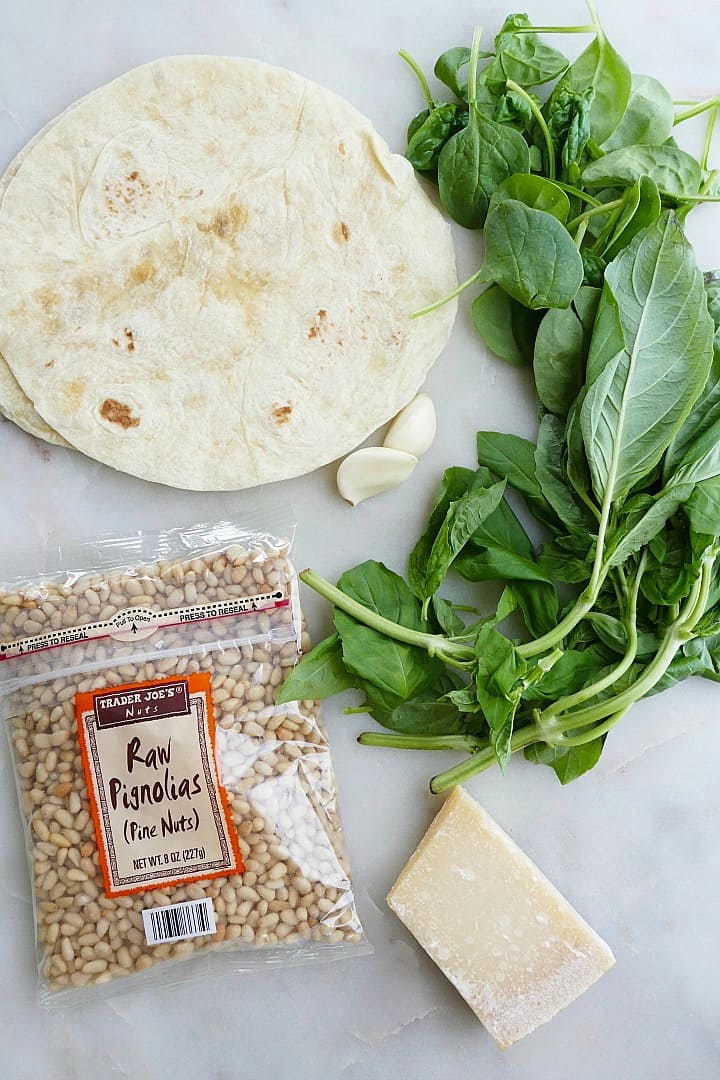 flour tortillas, pine nuts, parmesan cheese, and basil on a counter