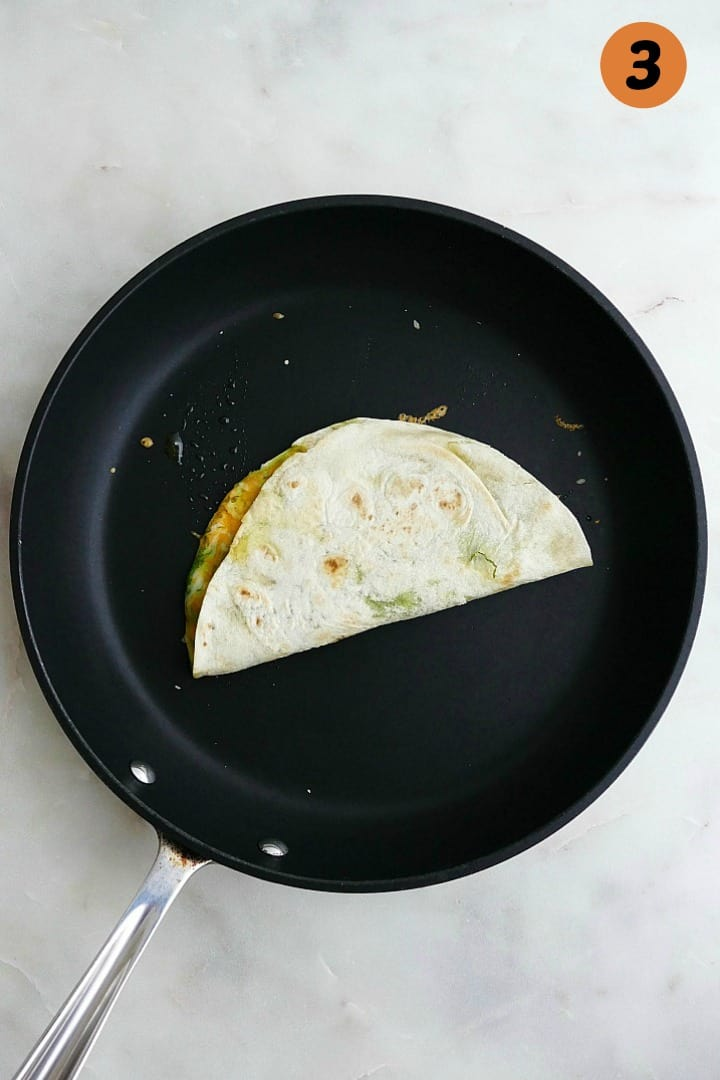 quesadilla cooking in a black skillet on a white counter