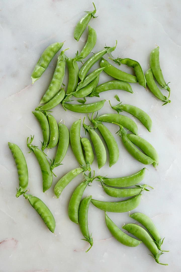 freshly picked sugar snap peas spread out on a white counter