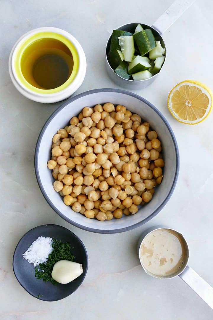 olive oil, pickles, garlic, spices, chickpeas, tahini, and lemon on a counter