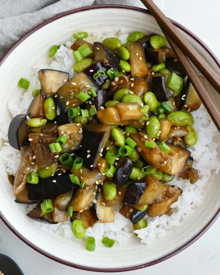 square image of eggplant teriyaki in a serving dish with brown chopsticks