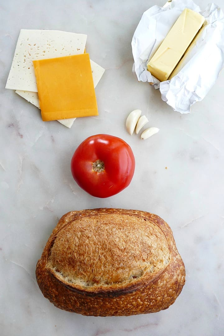 cheese slices, bread, garlic cloves, tomato, and butter spread out on a counter