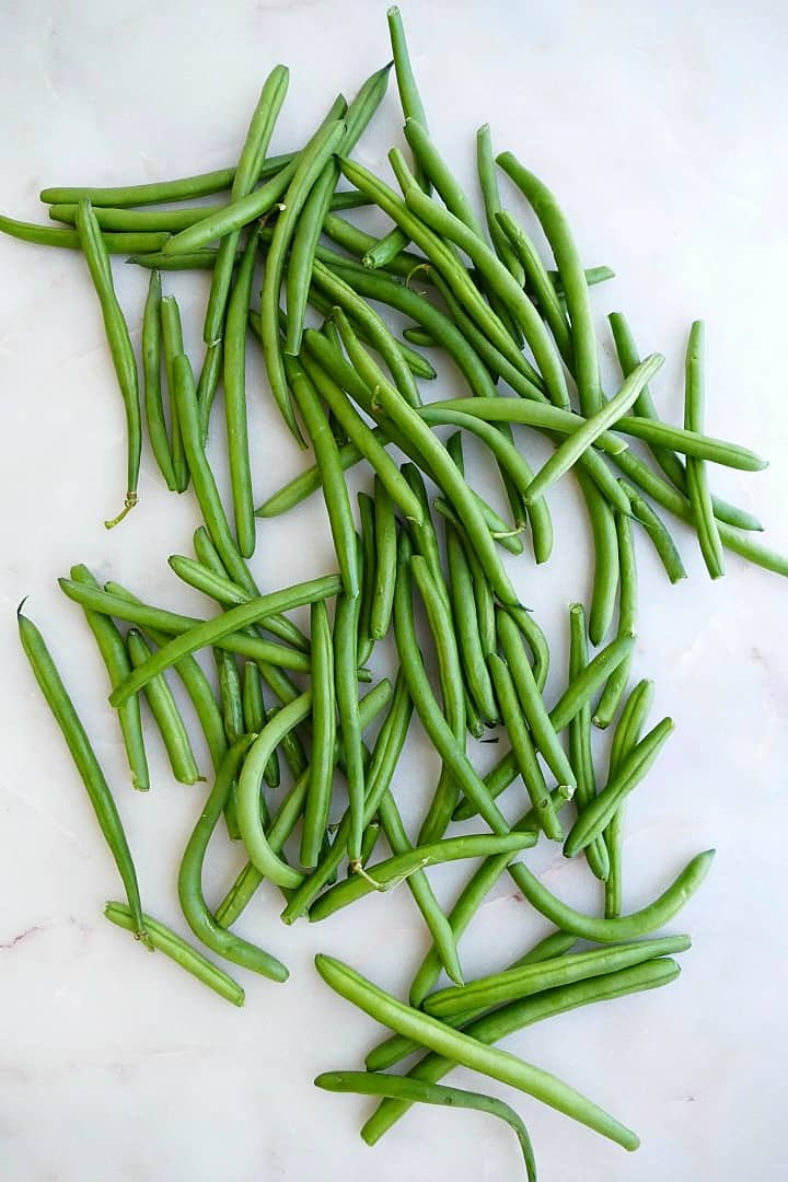 fresh green beans spread out next to each other on a white counter