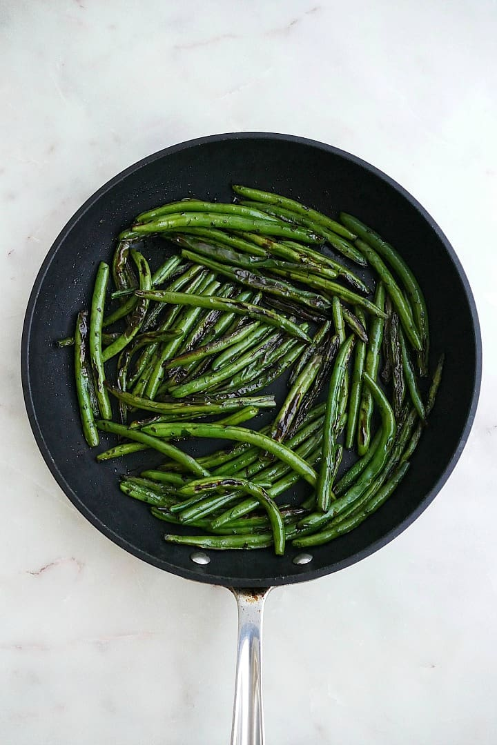 sauteed fresh green beans in a black skillet on a counter