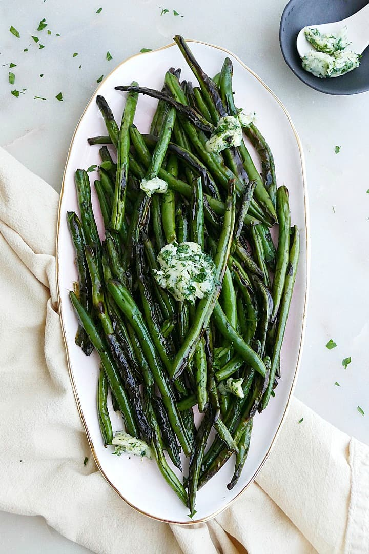 herb and garlic butter green beans displayed on an oval serving platter