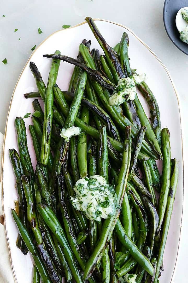 close up of garlic butter green beans on a serving platter topped with butter