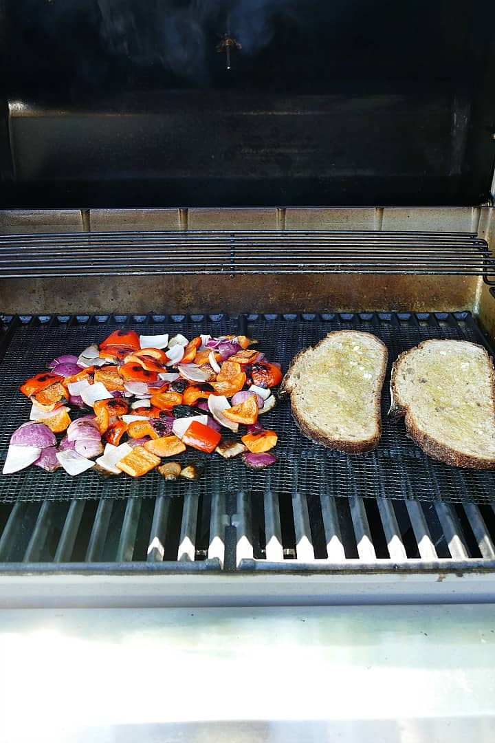 peppers, onions, and bread slices on top of grill mats on a grill