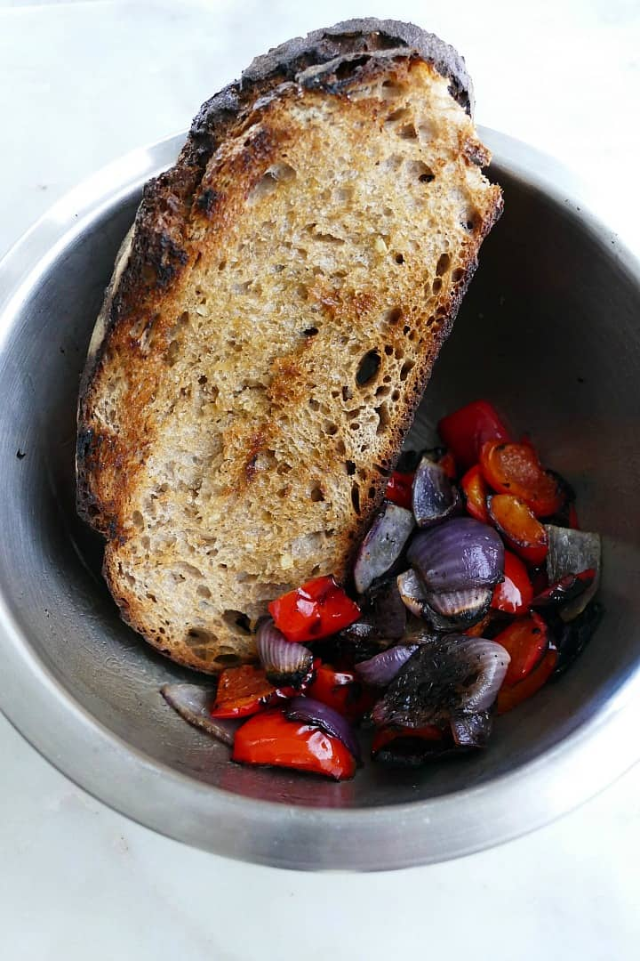 mixing bowl with grilled bread slices, peppers, and red onions on a counter