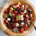 grilled panzanella salad in a wooden bowl with a serving spoon