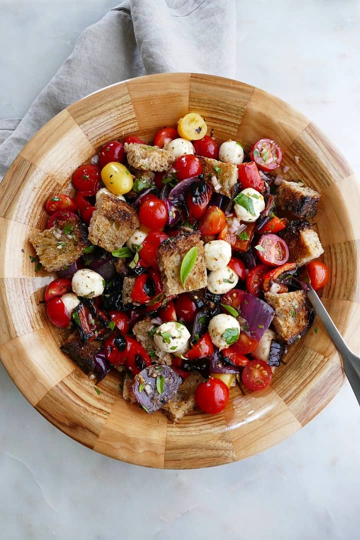 grilled panzanella salad in a wooden bowl with a serving spoon on a counter