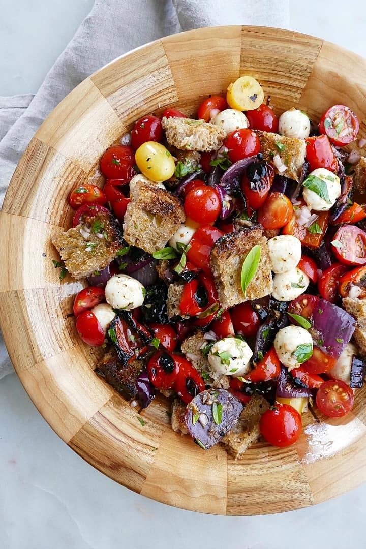 close up of grilled panzanella salad in a wooden bowl on top of a napkin