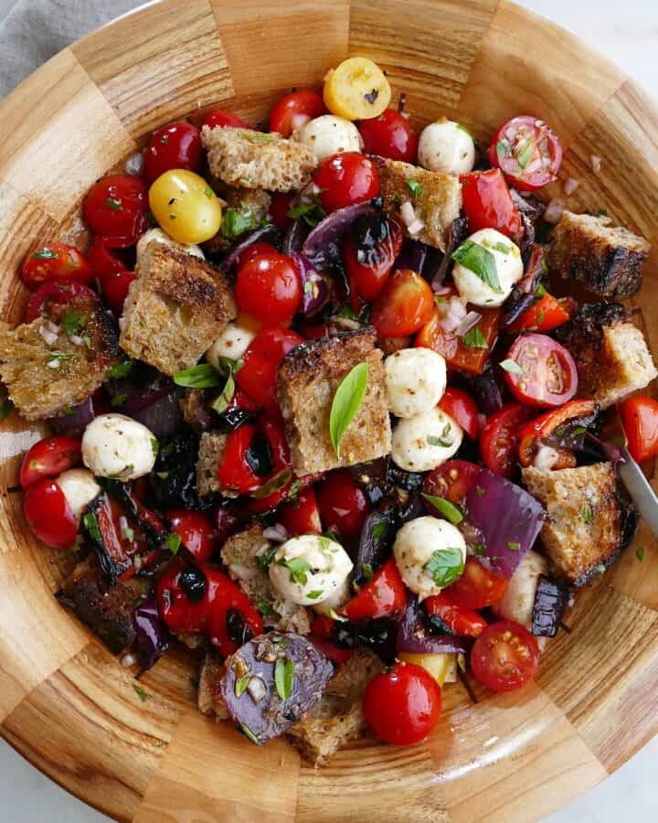 square image of grilled panzanella salad in a wooden bowl with a serving spoon