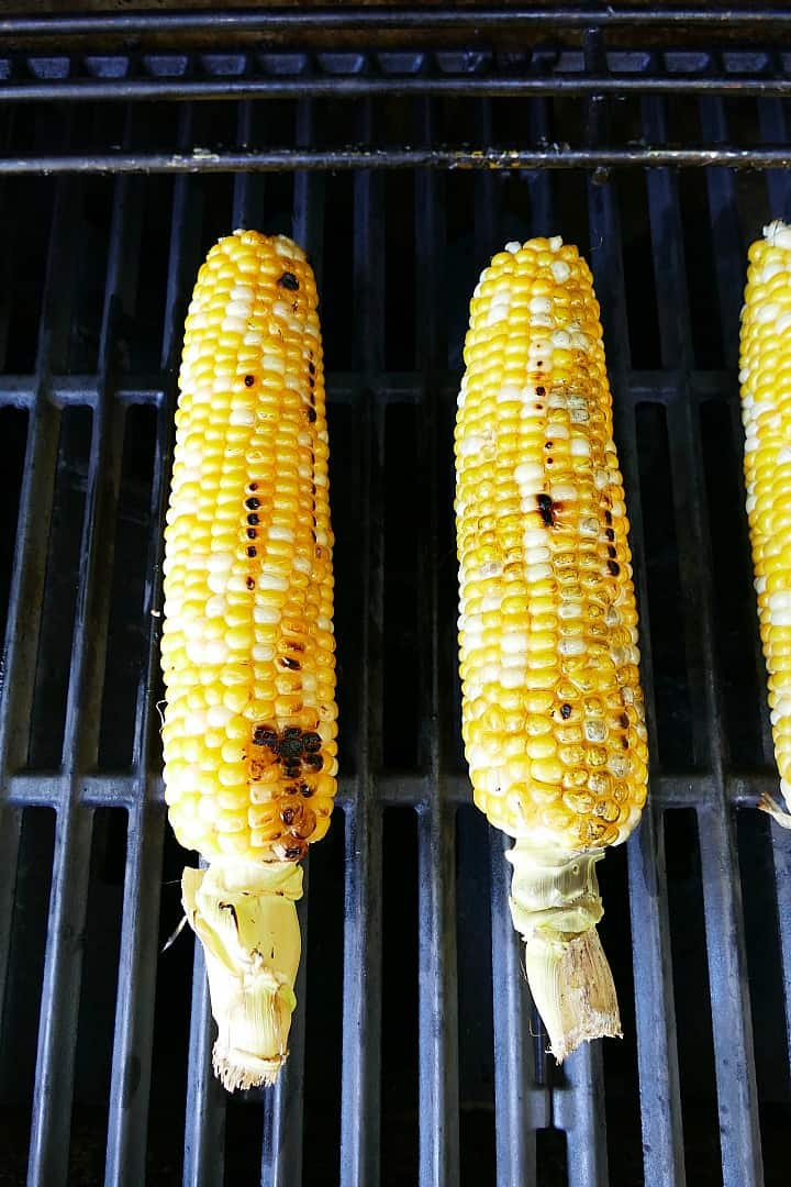 two cobs of corn on grill mats on top of an outdoor grill