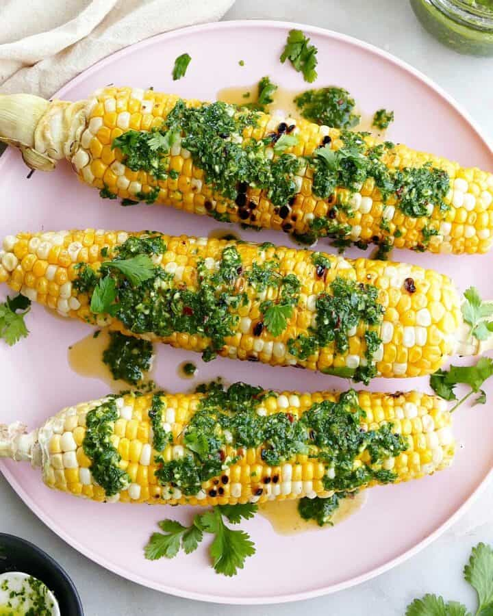 square image of three cobs of corn drizzled with chimichurri on a serving plate