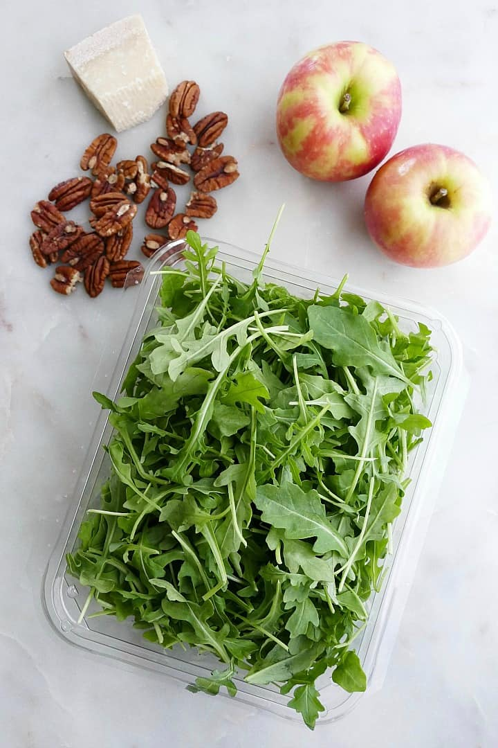 pecans, a block of parmesan, two apples, and arugula spread out on a counter