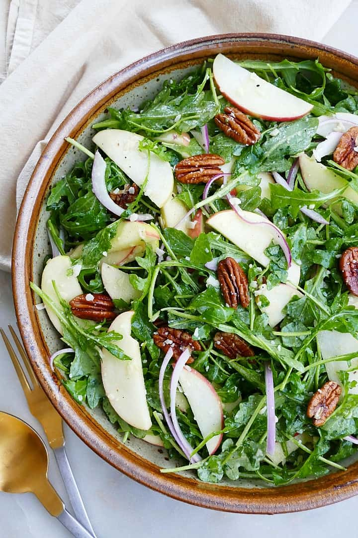close image of arugula salad with apples and pecans on a counter