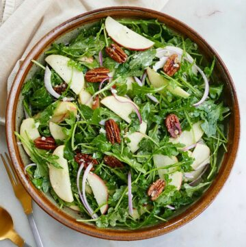 square image of arugula apple salad in a large serving bowl on a counter