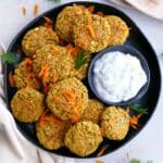 several carrot falafel patties on a serving dish with homemade tzatziki sauce