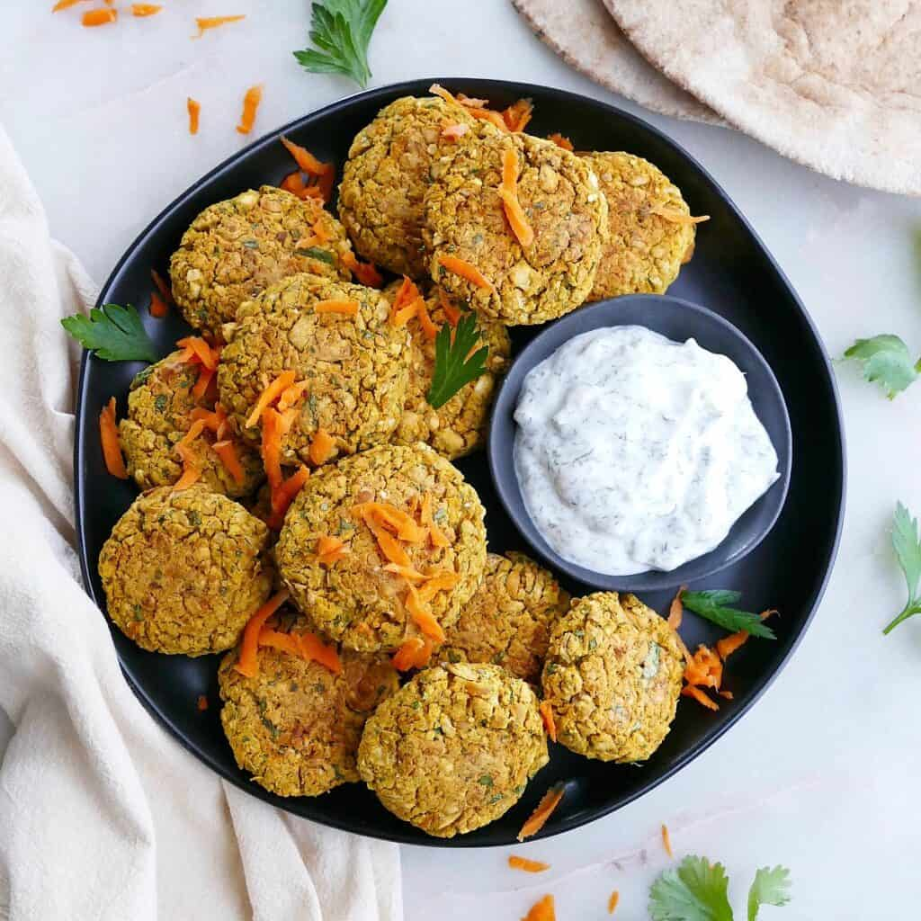 square image of baked curry carrot falafel on a platter with tzatziki