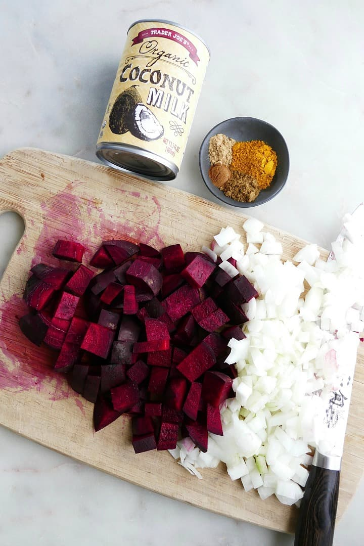 coconut milk, curry spices, diced beets and onions on a cutting board on a counter
