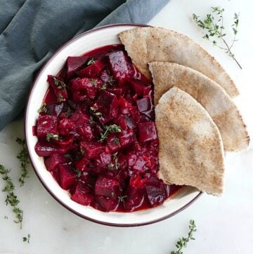 beetroot curry next to four slices of pita in a serving bowl on a counter