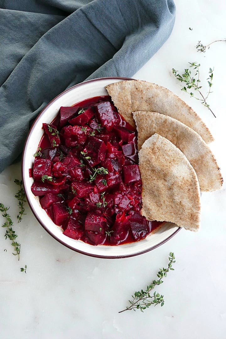 beetroot curry next to three slices of pita in a serving bowl on a counter