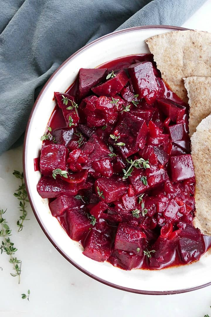 close-up image of beet curry with pita in a serving bowl on a counter
