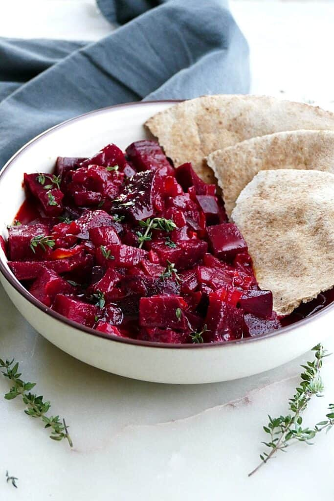 side angle of beetroot curry with pita surrounded by thyme leaves on a counter
