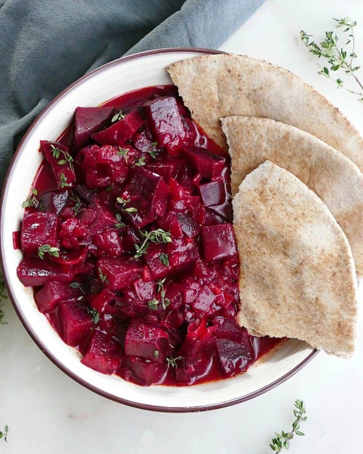 square image of beetroot curry and pita slices in a serving bowl