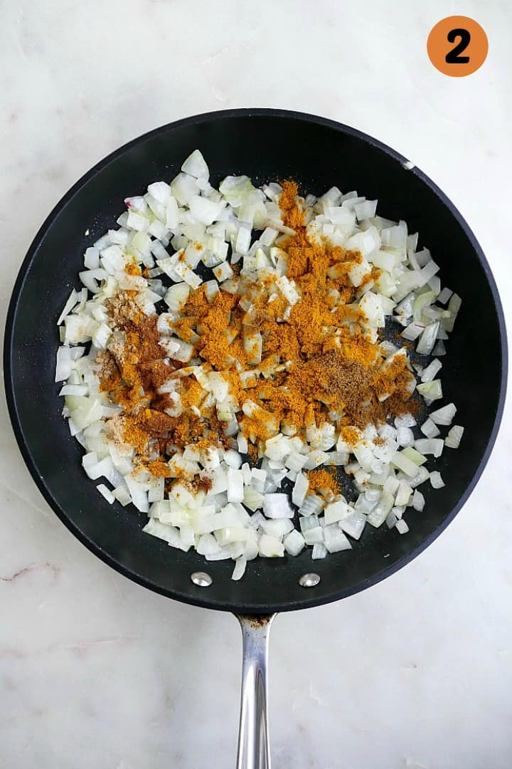 diced onions and curry spices cooking in a skillet with the number two in the corner