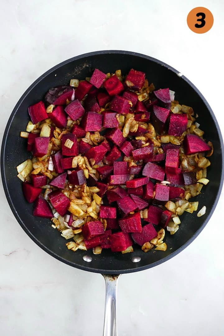 beets, onions, and curry spices cooking in a skillet with the number three in the corner