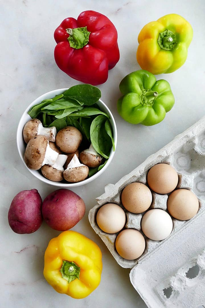 bell peppers, mushrooms, spinach, potatoes, and eggs spread out on a counter