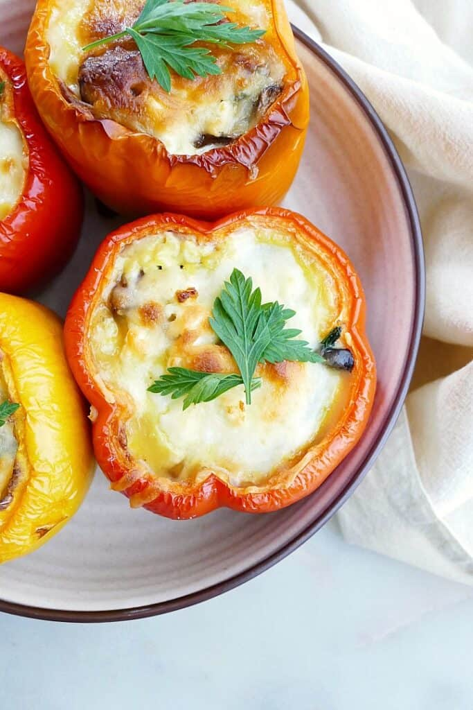 close-up image of a breakfast stuffed pepper topped with cheese and parsley on a serving platter