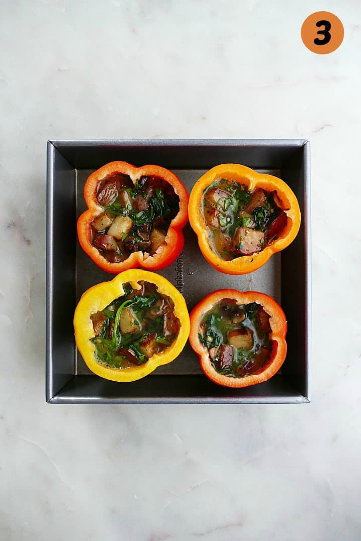 stuffed bell peppers in a baking dish on a counter with the number three in the corner