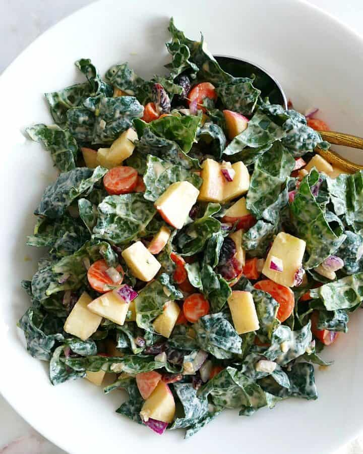 square image of kale salad with tahini dressing in a mixing bowl on a counter