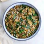 lentil risotto with collards in a serving bowl on a counter