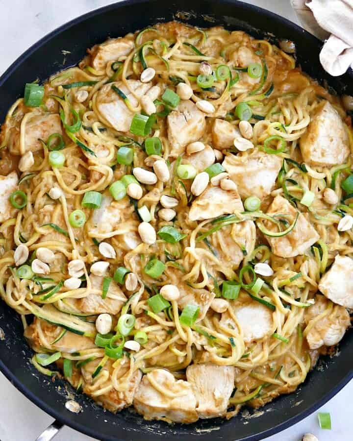 square image of peanut zucchini noodles with chicken in a skillet