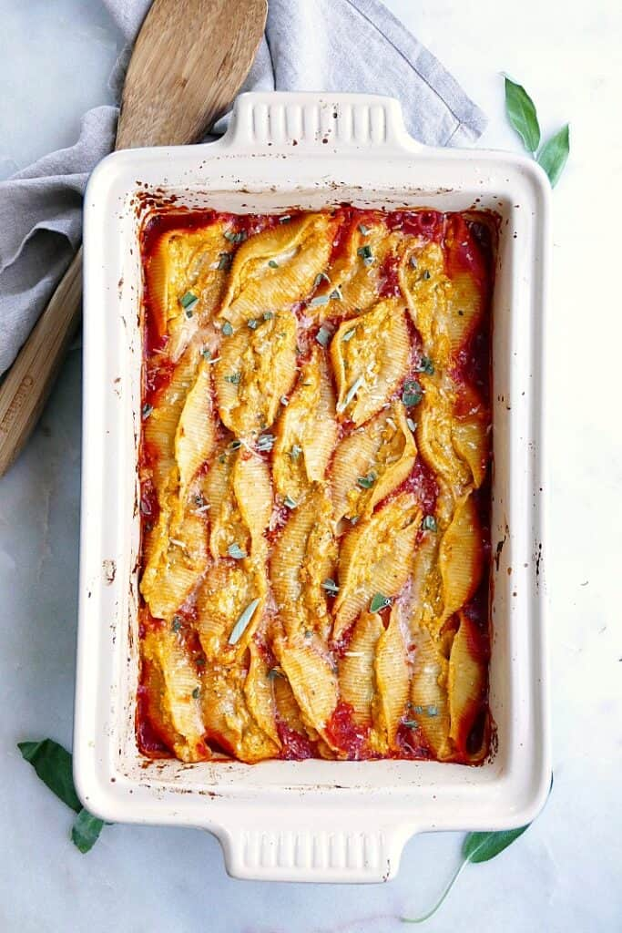 finished ricotta and pumpkin stuffed shells in a large baking dish on a counter