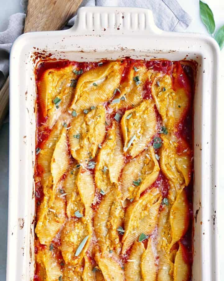 square image of pumpkin stuffed shells in a baking dish on a counter