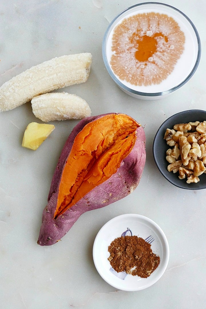 frozen banana, cooked sweet potato, ginger, spices, walnuts, and coconut milk on a counter