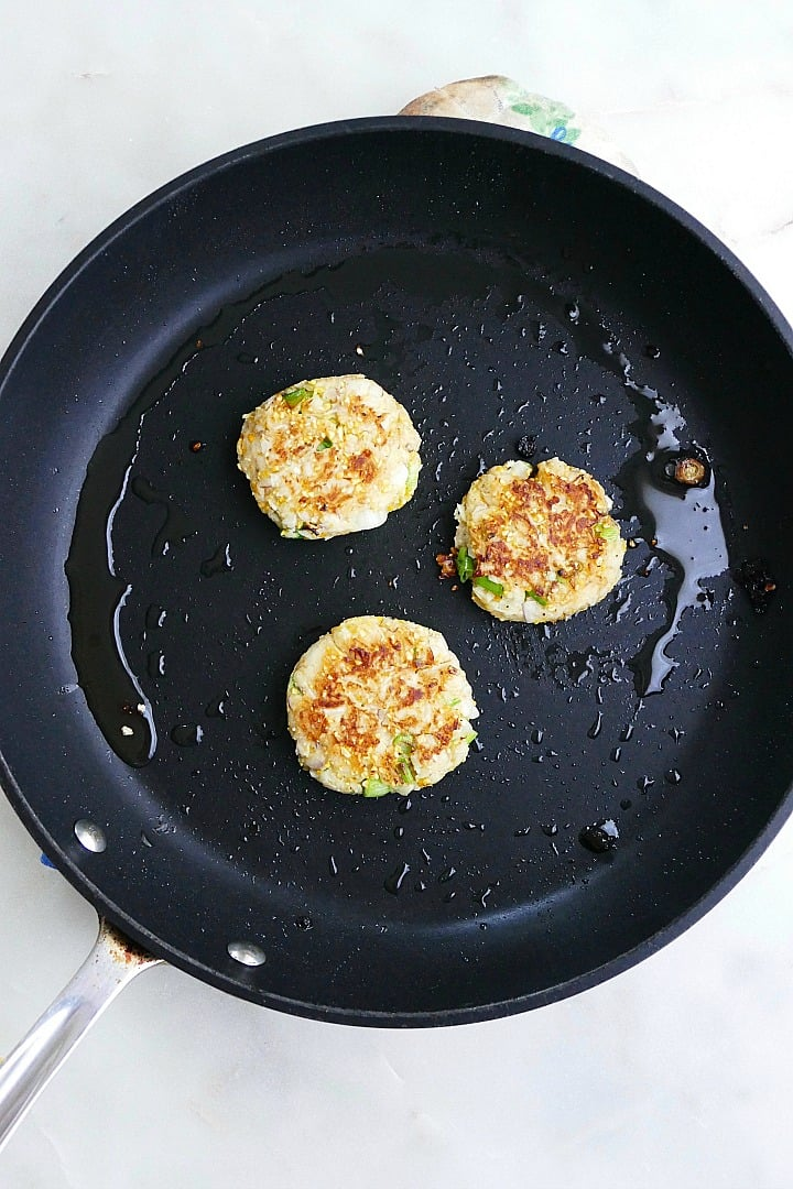 three turnip cakes in a large skillet cooking in oil
