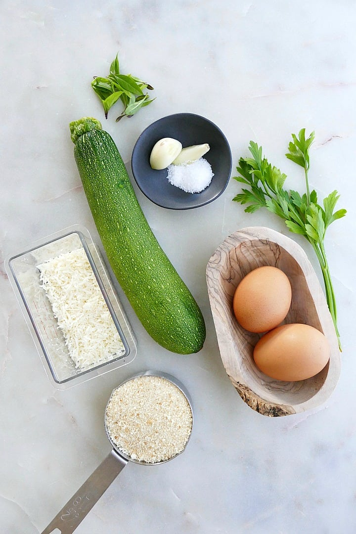 zucchini, garlic, herbs, eggs, bread crumbs, and parmesan cheese on a counter