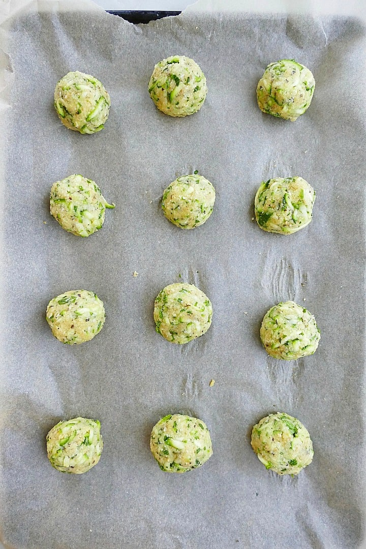 12 zucchini balls spread out on a baking sheet lined with parchment paper