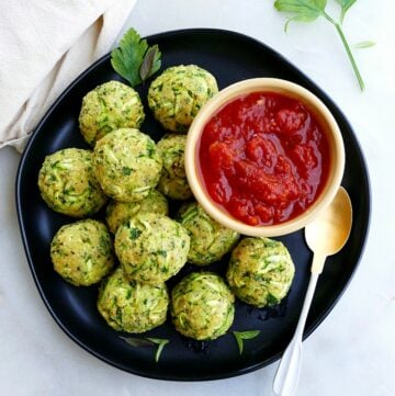 zucchini balls on a serving plate with tomato sauce in a small bowl