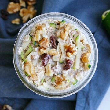 overhead shot of zucchini overnight oats in a jar topped with walnuts and raisins