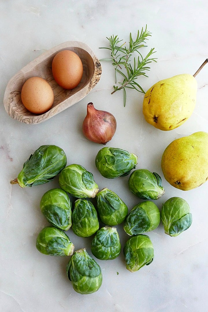 raw brussels sprouts, shallot, pears, and rosemary next to a couple eggs on a counter