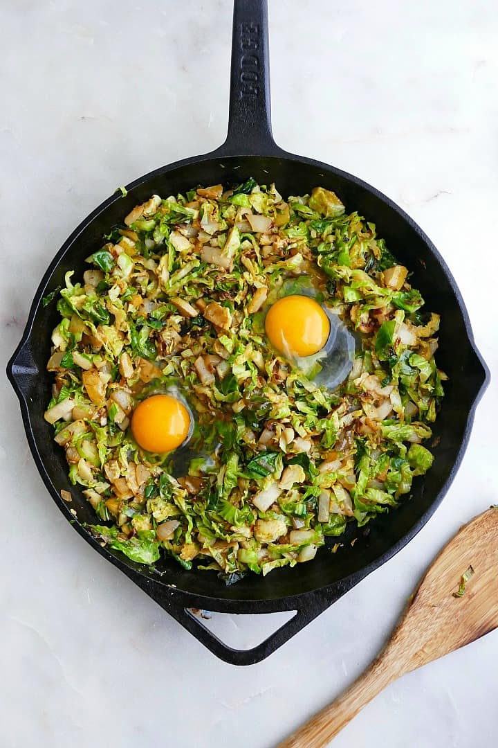 brussels sprouts cooked down in a skillet with two cracked eggs on top on a counter