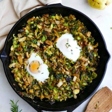 cast iron skillet with sauteed brussels sprouts and fried eggs on a counter next to serving spoon