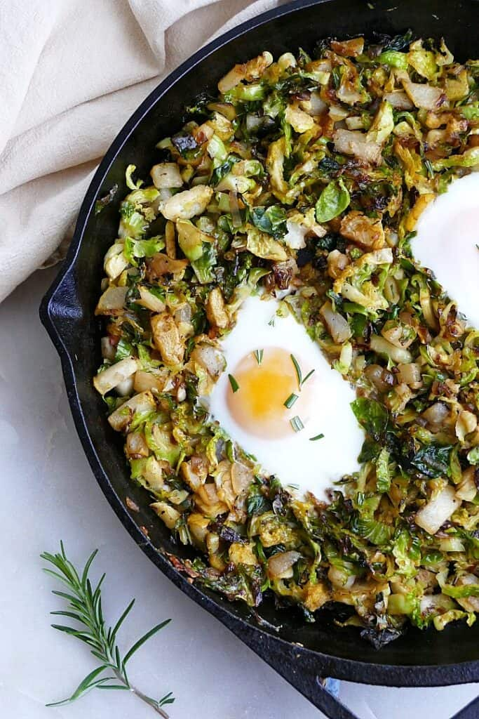 cooked Brussels sprouts and eggs breakfast hash topped with rosemary on a counter
