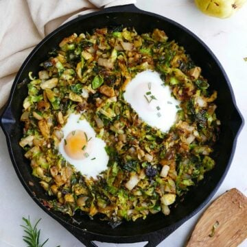square image of Brussels sprouts and eggs hash in a cast iron skillet on a counter